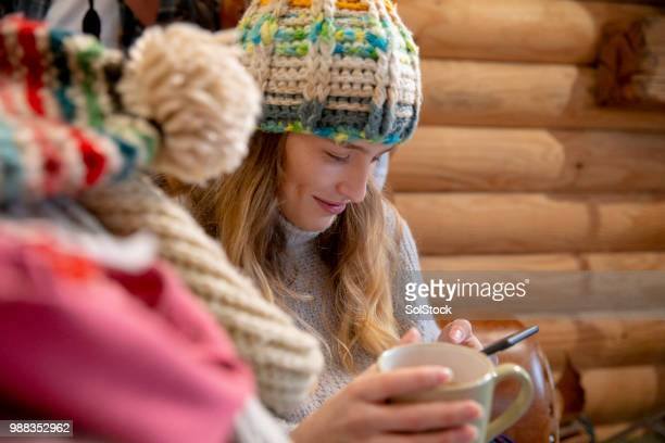 young woman using her phone in the log cabin - knit hat stock pictures, royalty-free photos & images