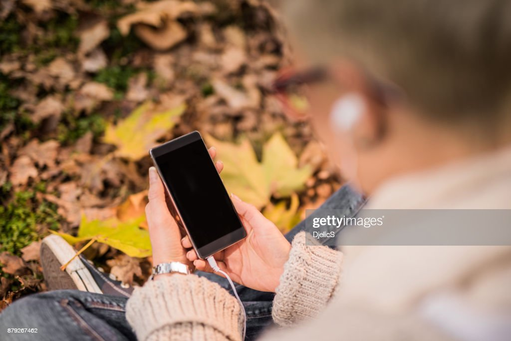 Young woman using her smart phone on autumn leaves background. : Stock Photo