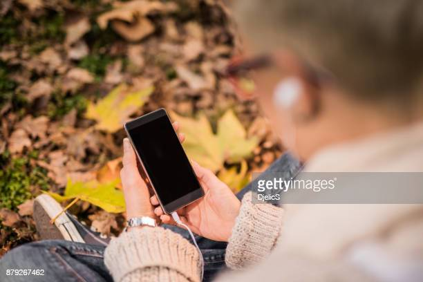 young woman using her smart phone on autumn leaves background. - iphone mockup stock pictures, royalty-free photos & images
