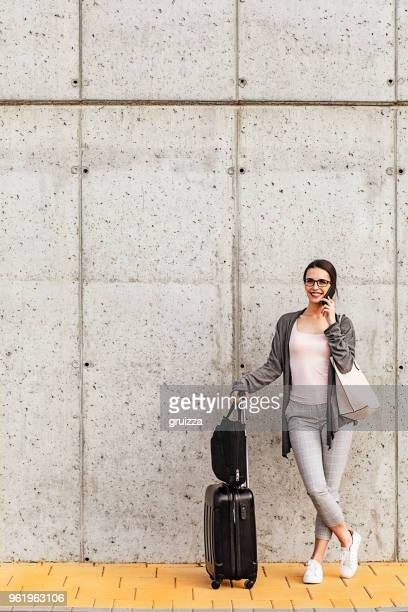 young woman using her smart phone standing beside the concrete wall - wheeled luggage stock photos and pictures