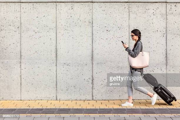 young woman using her smart phone walking beside the concrete wall and pulling a small wheeled luggage with a briefcase on it - business travel stock pictures, royalty-free photos & images