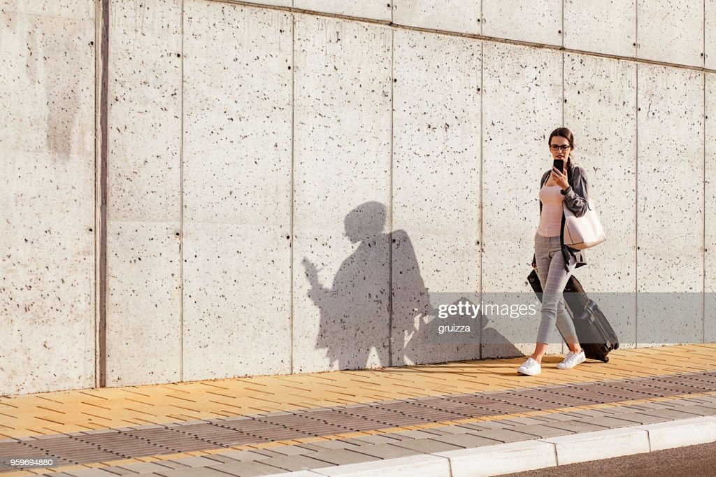 Young woman using her smart phone while walking beside the concrete wall and pulling a small wheeled luggage with a briefcase on it : Stock Photo