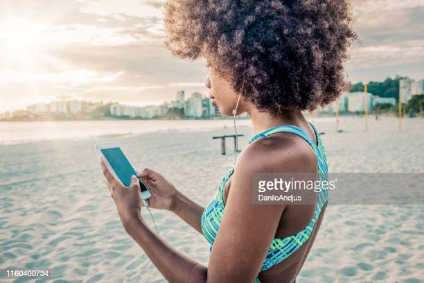 young woman using her smartphone after exercising - social media marketing stock pictures, royalty-free photos & images