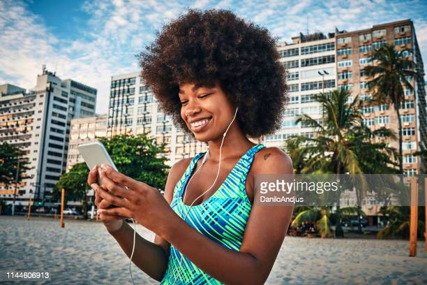 young woman using her smartphone and listening to music after exercising - social media marketing stock pictures, royalty-free photos & images