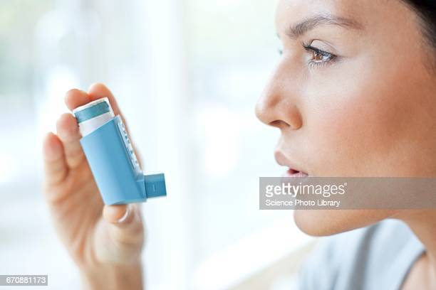 young woman using inhaler - asthma inhaler stock pictures, royalty-free photos & images
