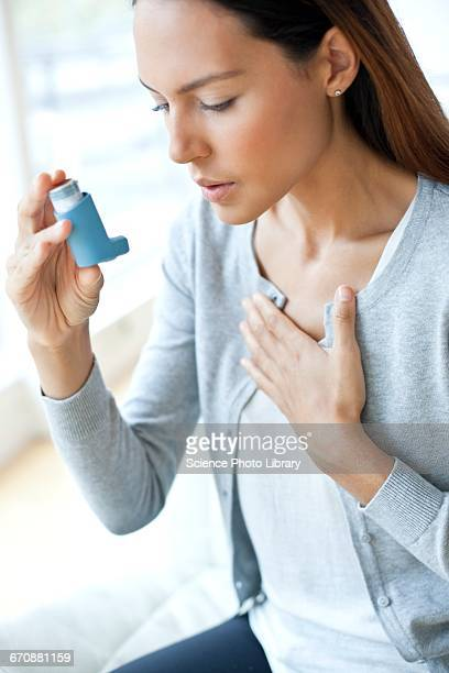 Young woman using inhaler touching chest