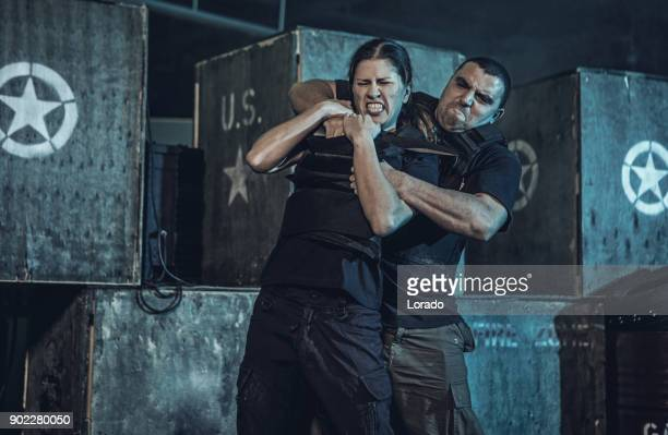 young woman using krav maga fighting self defense against male assailant in dark indoor urban setting - self defence stock pictures, royalty-free photos & images