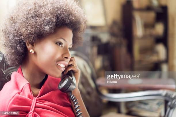 junge Frau mit Festnetz-Telefon