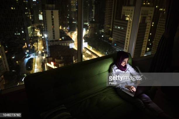young woman using laptop after work - muslim woman darkness stock photos and pictures