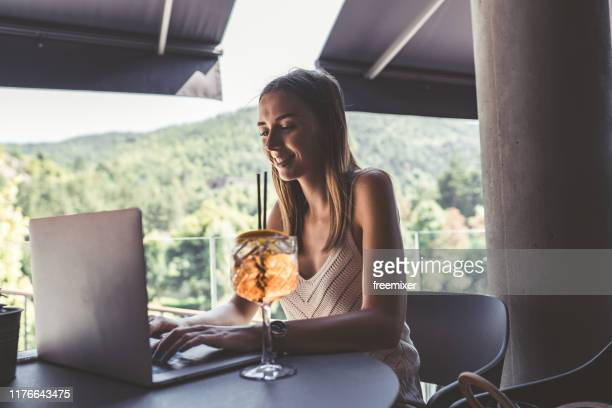young woman using laptop and drinking aperitif - one young woman only stock pictures, royalty-free photos & images