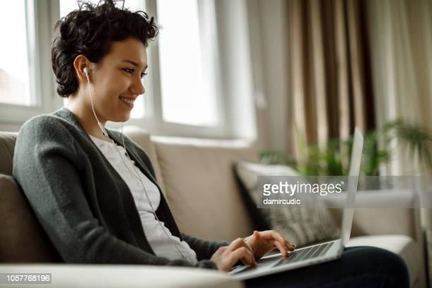 jonge vrouw met laptop en luisteren naar muziek thuis - voip stockfoto's en -beelden