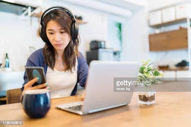 自宅でラップトップとスマートフォンを使用する若い女性 - ブルートゥース ストックフォトと画像