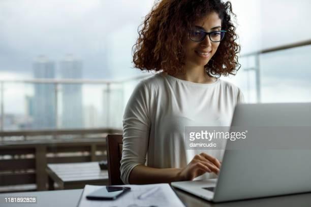 jonge vrouw met laptop in een café - midden oosterse etniciteit stockfoto's en -beelden