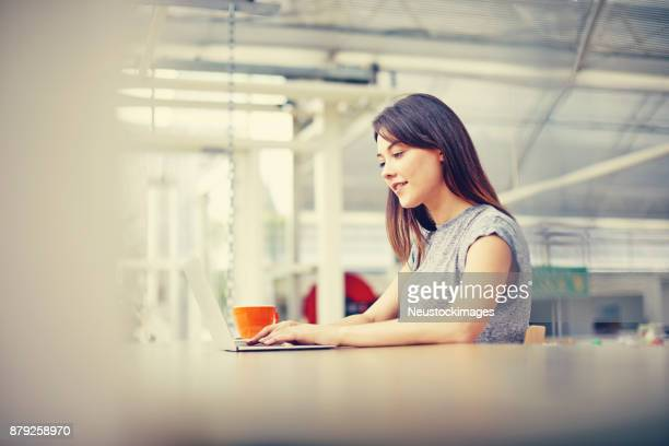 Young woman using laptop at cafe table