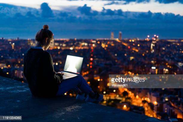 young woman using laptop at dawn above the city, barcelona, spain - technology fotografías e imágenes de stock
