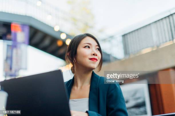 young woman using laptop at sidewalk cafe - working stock pictures, royalty-free photos & images