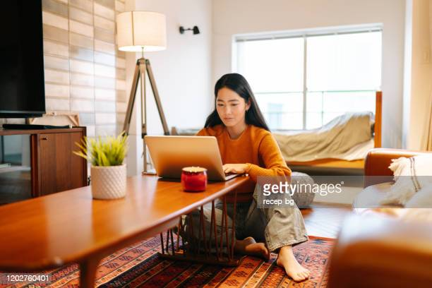 young woman using laptop comfortably at home - online class stock pictures, royalty-free photos & images