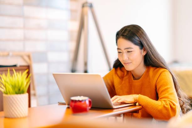年輕女子在家中舒適地使用筆記本電腦 - 聯繫 個照片及圖片檔