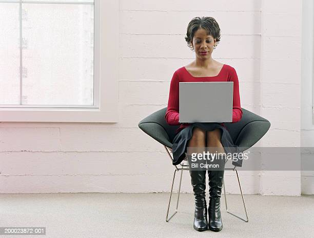 young woman using laptop computer - work shoe stock photos and pictures