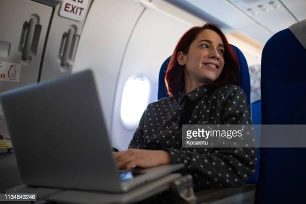 フライト中にラップトップを使用している若い女性 - 乗り物に乗って ストックフォトと画像