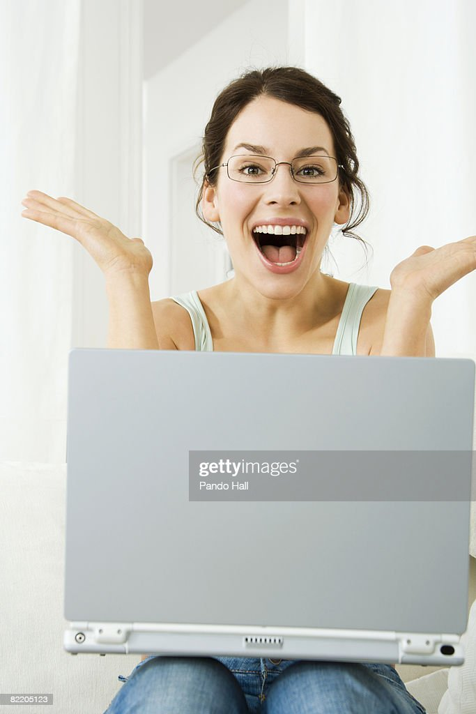 Young woman using laptop, eyes and mouth wide open : Stock Photo