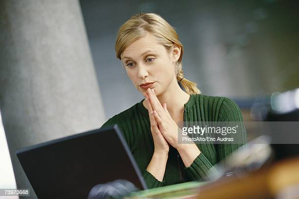 Young woman using laptop, hands clasped in front of chin