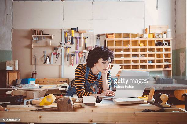 Young woman using laptop in a carpentry workshop