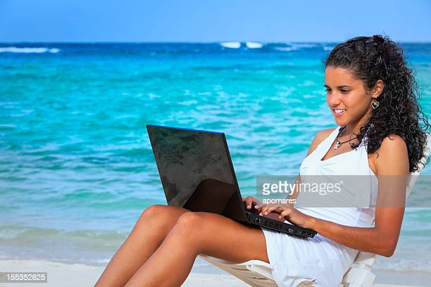 Young woman using laptop in a tropical turquioise beach