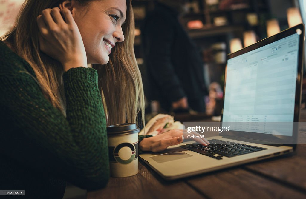 Young woman using laptop in cafe : Stock Photo