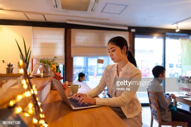 カフェでノート パソコンを使用しての若い女性