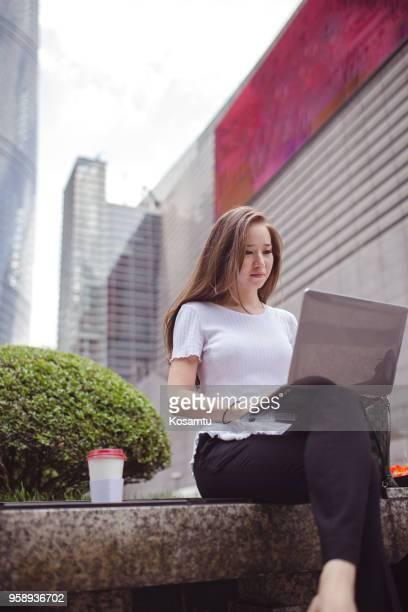 Jeune femme à l'aide de portable dans le quartier financier