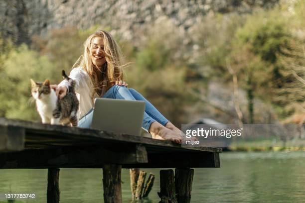 jeune femme utilisant l'ordinateur portatif dans la nature - une seule jeune femme photos et images de collection