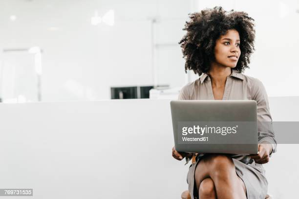 young woman using laptop in office - afro frisur stock-fotos und bilder