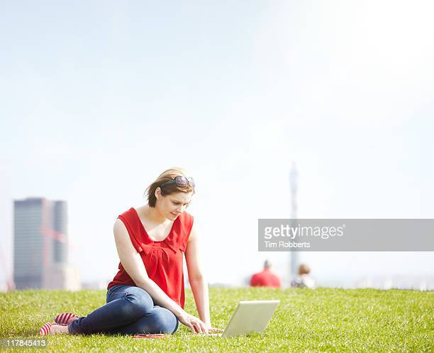 Young woman using laptop in urban park
