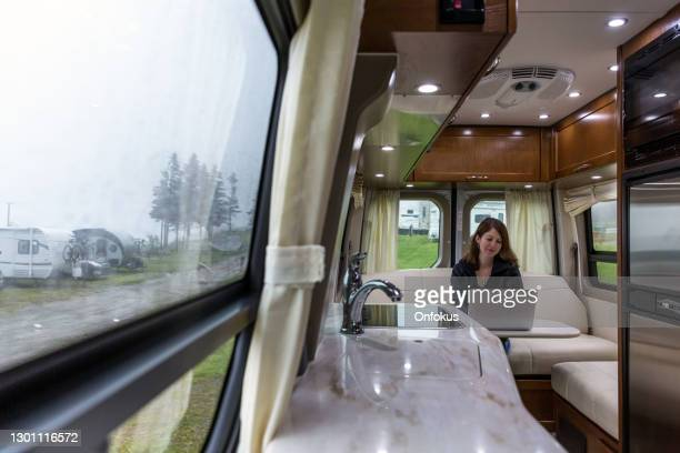young woman using laptop inside motor home - borough district type stock pictures, royalty-free photos & images