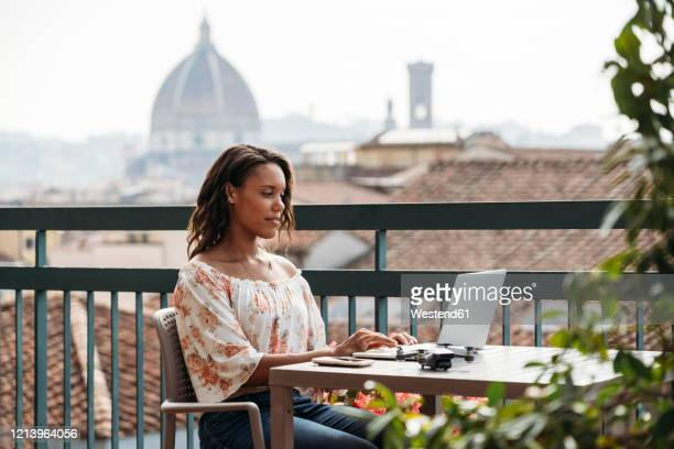 young woman using laptop on a balcony in florence, italy - italy stock pictures, royalty-free photos & images