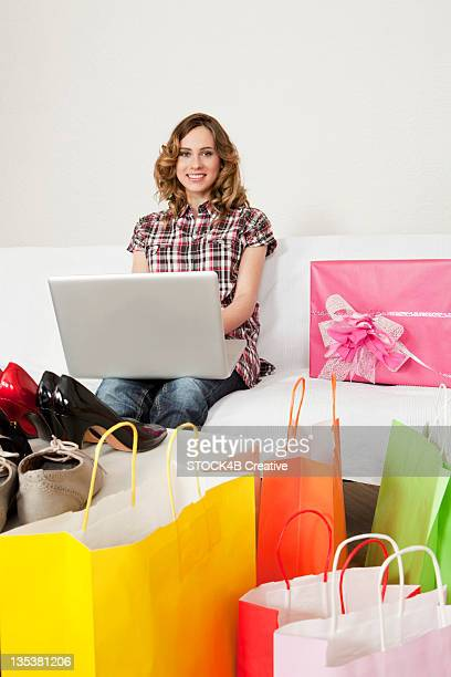Young woman using laptop on couch surrounded by shopping bags and new shoes