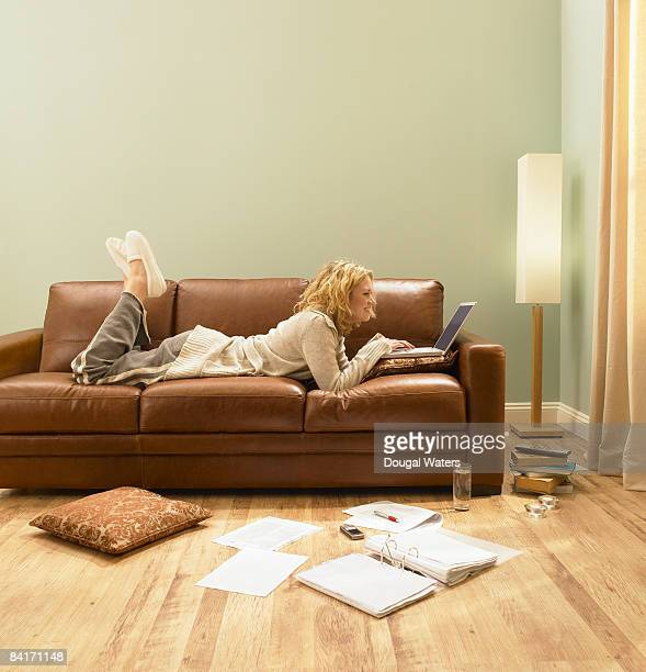 young woman using laptop on sofa. - 腹ばい ストックフォトと画像