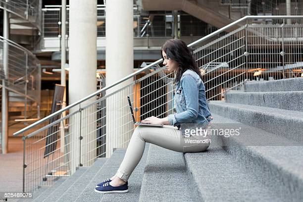 Young woman using laptop on stairs
