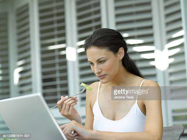 young woman using laptop outdoors - ポニーテール ストックフォトと画像