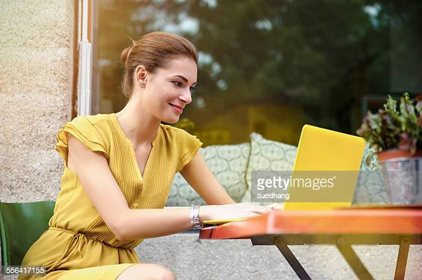 Young woman using laptop outside cafe