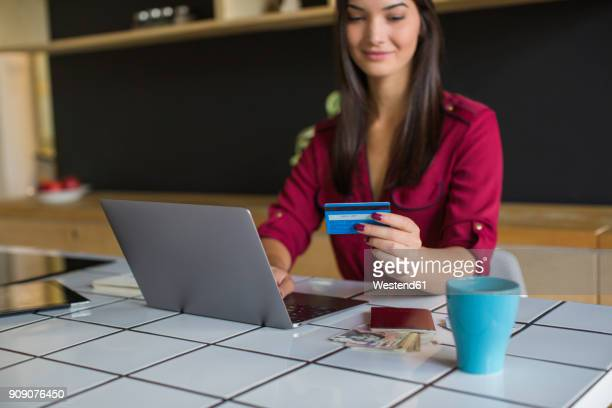 Young woman using laptop, paying with credit card