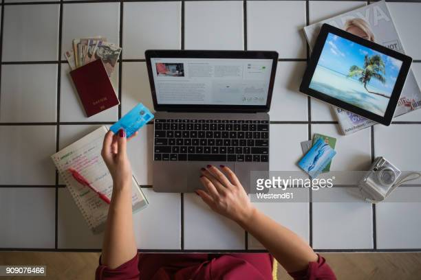 Young woman using laptop, paying with credit card, travel booking