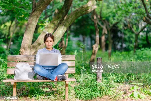 公共の公園で平和的にラップトップを使用して若い女性 - フリーランス ストックフォトと画像