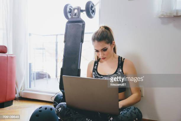 Young woman using laptop while electric skateboard is chragig