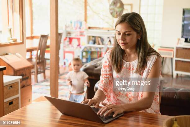 Young woman using laptop with baby son in background