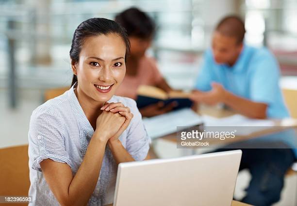 Young woman using laptop with friends at the back