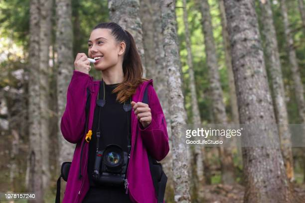 young woman using lip balm in nature - lip balm stock pictures, royalty-free photos & images