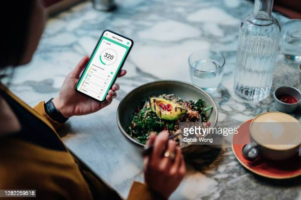 young woman using meal planning mobile app for a healthy diet - crucifers stock pictures, royalty-free photos & images