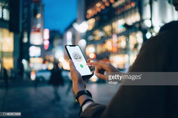 young woman using mobile app on smart phone to arrange taxi ride in downtown city street, with illuminated city traffic scene as background - mobile app stock pictures, royalty-free photos & images
